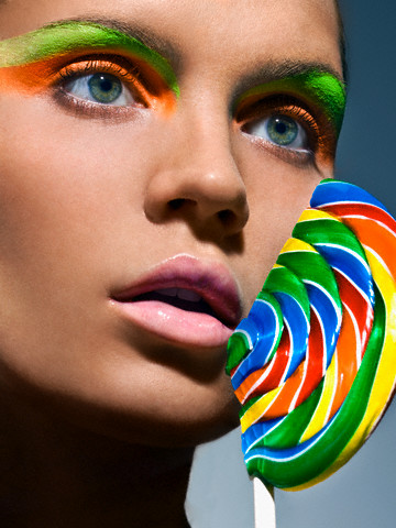 Woman Wearing Bright Eyeshadow and Holding Lollipop